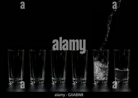 in glass beakers pure water is poured on a dark background - Stock Photo
