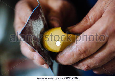 Close up of craftsman's hands sanding knife handle - Stock Photo