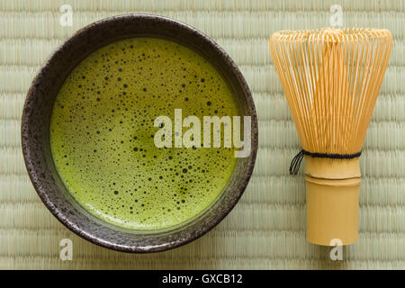Japanese Matcha green tea in a chawan or traditional ceramic bowl with a chasen or bamboo whisk - Stock Photo