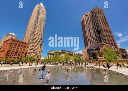 People relax near fountain in the Cleveland center Public Square, Cleveland, OH - Stock Photo