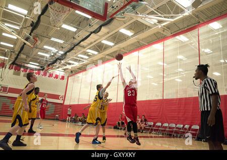 Teen basketball player leaps in air to make jump shot. North High School White Bear Lake Minnesota MN USA - Stock Photo