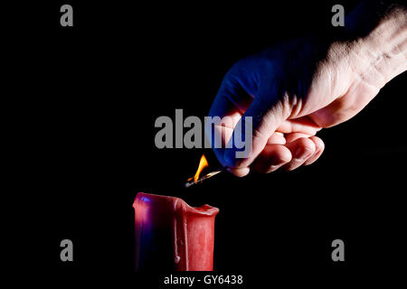 human hand with a match lights a red candle on the black background - Stock Photo