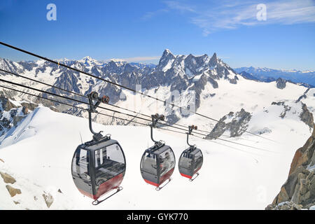 Tourists enjoying the majestic landscape in gondolas from Point Helbronner to Aiguille du Midi, France - Stock Photo