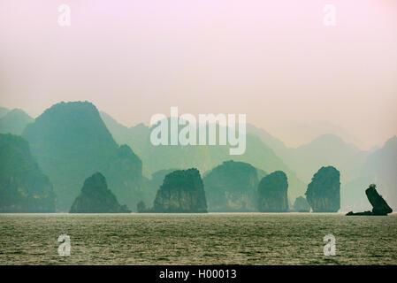 Limestone boulders, karst mountains in Halong bay ,fog, haze, Gulf of Tonkin, North Vietnam, Vietnam - Stock Photo