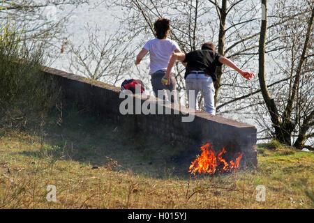 Jugendliche entfachen ein Feuer und ergreifen die Flucht, um sich einer Bestrafung zu entziehen, Deutschland | teens - Stock Photo