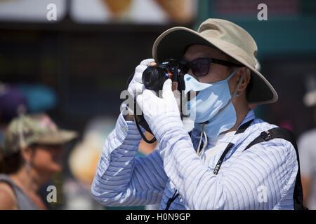 Man with protective mask taking photos at Venice Beach, California, USA - Stock Photo