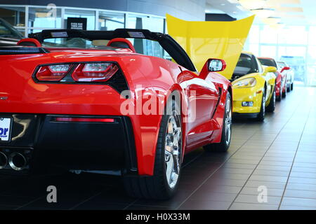 row of chevy corvette sports cars sit on display in dealership showroom, waiting to be sold - Stock Photo