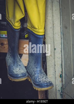 Dirty used rubber wellingtons hanging on a rack in a wooden shed in the garden - Stock Photo