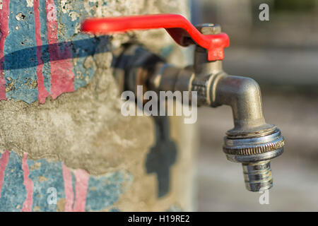 Faucet on Old Cracked Blue Painted Wall. Red Handle Water Tap Outdoor Background. Save Water Concept. - Stock Photo