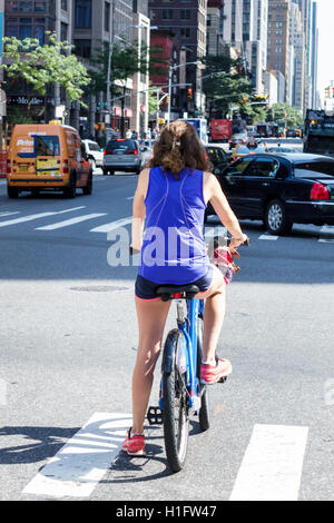 Manhattan New York City NYC NY Chelsea 6th Sixth Avenue street traffic woman bicycle cycle stopped intersection - Stock Photo