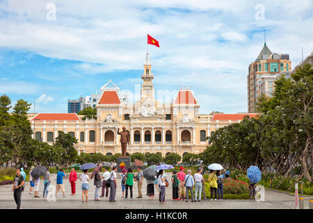 Tourists at Ho Chi Minh Statue in front of People's Committee Building. Ho Chi Minh City, Vietnam. - Stock Photo