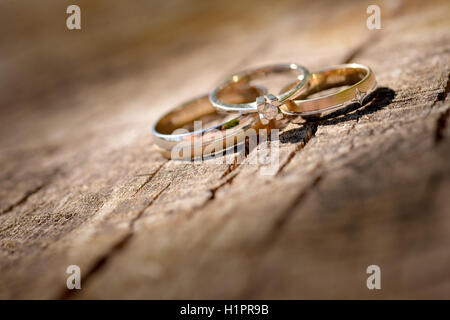 Gold wedding ring placed on a wood surface - Stock Photo