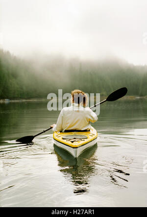 A guest at Nimmo Bay resort goes for a morning kayak. Nimmo Bay is an angler's paradise set in the wilderness of - Stock Photo