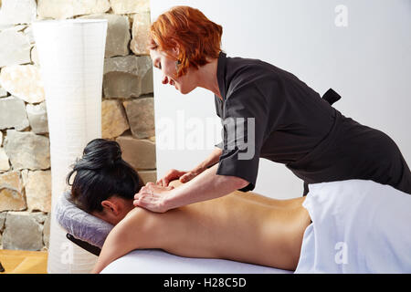 massage in woman back with physiotherapist indoor - Stock Photo