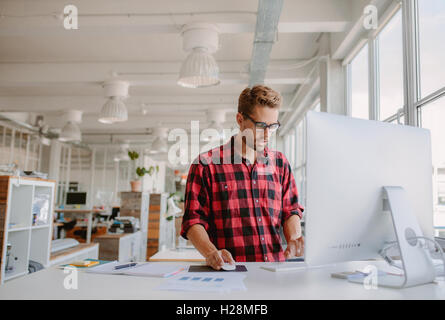 Young man working on computer. Caucasian male office worker using desktop pc in modern office. - Stock Photo