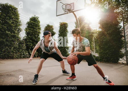 Teenage friends playing streetball against each other and having fun. Two young men having a game of basketball - Stock Photo
