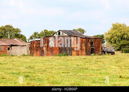 Rusty corrugated iron old farm buildings Cheshire England UK - Stock Photo