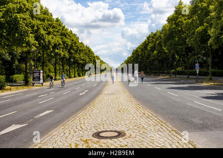 Family walks and people ride bikes on street called 'Strase des 17. Juni' at very big park 'Tiergarten' in Berlin. - Stock Photo
