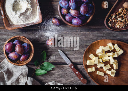Ingredients for plum pie: fresh plums, walnuts, flour with sugar and chopped butter on rustic wooden table. Overhead - Stock Photo