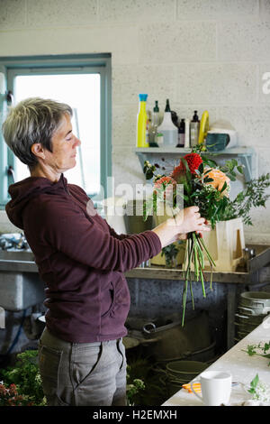 Organic flower arrangements. A woman creating a hand tied bouquet. - Stock Photo
