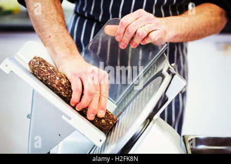 Close up of a butcher wearing a striped blue apron , slicing salami with a slicer. - Stock Photo