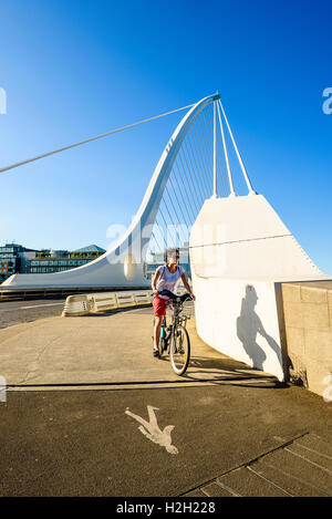 Cyclist at south end of Samuel Beckett Bridge over River Liffey Dublin Ireland - Stock Photo