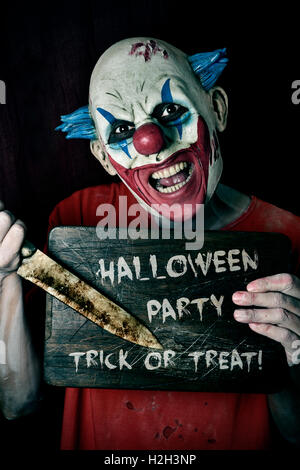 a scary evil clown pointing a big knife at a wore chopping board with the text Halloween party trick or treat written - Stock Photo