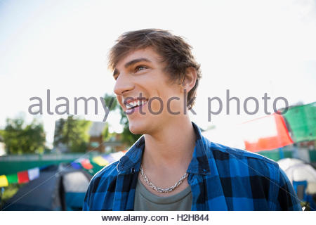 Portrait smiling young brunette man looking away at summer music festival campsite - Stock Photo