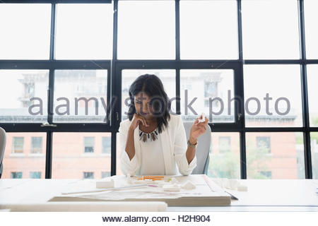 Female architect reviewing model at table in office - Stock Photo