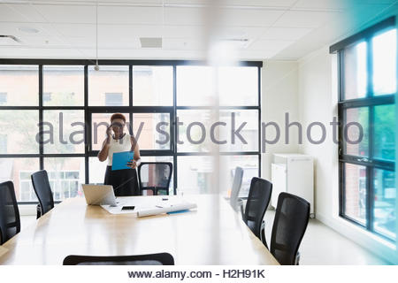 Female architect talking on cell phone in conference room - Stock Photo