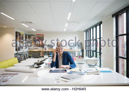 Smiling female architect talking on cell phone and using digital tablet at table in office - Stock Photo