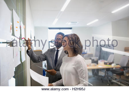 Businessman and businesswoman discussing hanging paperwork in office - Stock Photo