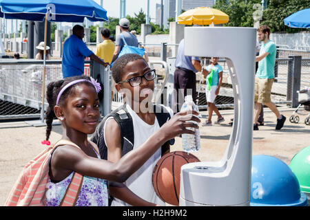 Brooklyn New York City NYC NY Brooklyn Bridge Park Pier 6 public park water fountain Black boy girl filling bottle - Stock Photo