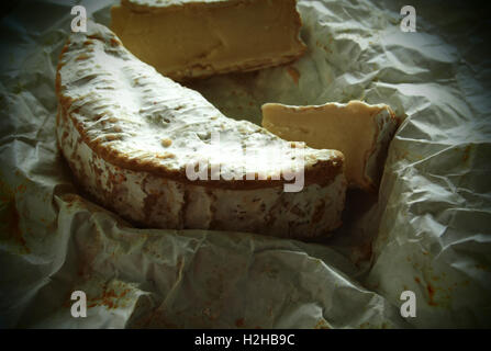 Camembert on crumpled wrapping paper. Grunge style. - Stock Photo