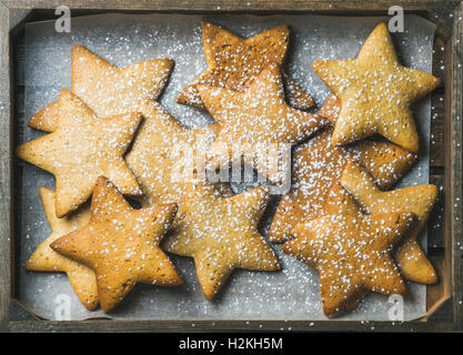 Sweet Christmas holiday gingerbread cookies in shape of stars with sugar powder on baking paper in rustic wooden - Stock Photo