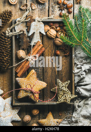Gingerbread star shaped cookies, wooden angels, decorative stars, nuts and spices in wooden tray with sugar powder - Stock Photo