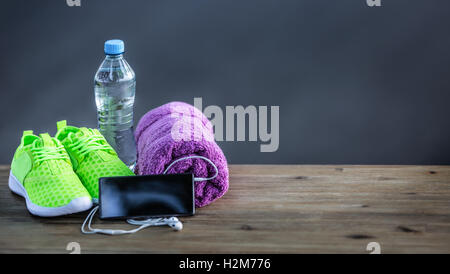 Pair of yellow green sport shoes towel water smart pone and headphones on wooden board. In the background forest - Stock Photo