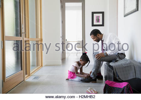 Daughter helping father tie shoes in morning foyer - Stock Photo