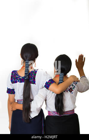 Beautiful hispanic mother and daughter wearing traditional andean clothing, both embracing while waving, seen from - Stock Photo