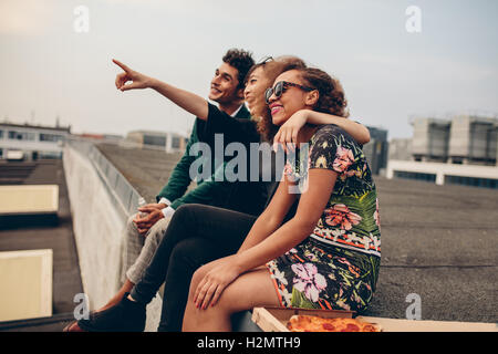 Man and women sitting on roof terrace and looking away smiling. Happy young friends relaxing on rooftop, with woman - Stock Photo