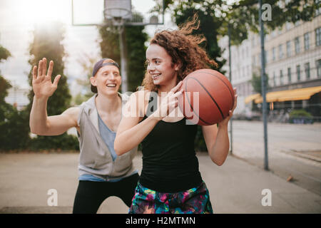 Young girl playing basketball with boy blocking. Teenage friends enjoying a game of streetball on outdoor court. - Stock Photo