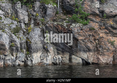 A view of the harsh rocky shore of Ladoga lake, overgrown with moss and shrubs. - Stock Photo