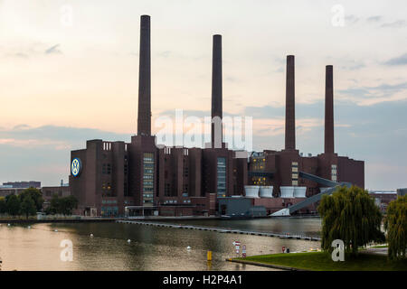 View of the old Volkswagen factory building with the illuminated VW logo - Stock Photo