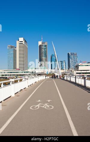 Vilnius, Lithuania - March 16, 2015: White bridge - pedestrian and bicycle bridge across Neris river, modern buildings. - Stock Photo