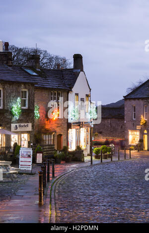 Colourful Christmas lights brighten up a dark winter's evening - Grassington Village, Yorkshire Dales National Park, - Stock Photo