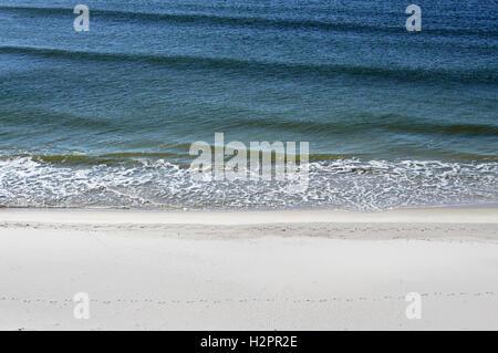 Blue waves rolling up onto white sand beaches of  Perdido Key. - Stock Photo