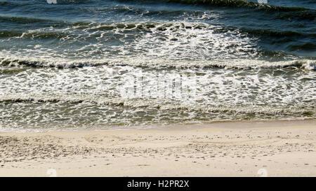 Foamy waves rolling up onto white sand beaches of Perdido Key. - Stock Photo