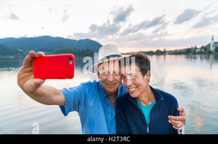 Man and woman smiling, taking photo with mobile phone, selfie, Schliersee, Upper Bavaria, Bavaria, Germany - Stock Photo
