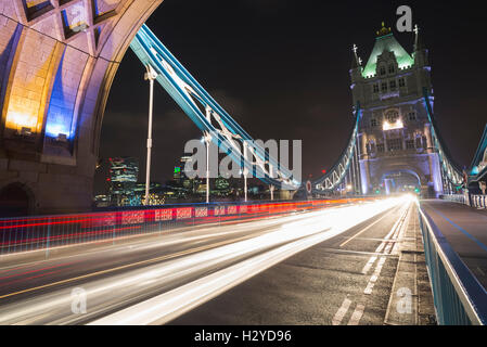 Skyline of City of London and gleam of traffic on the Tower Bridge over the river Thames at night, London, UK - Stock Photo