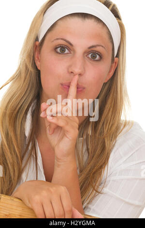 Young woman holding her finger in front of her mouth - Stock Photo